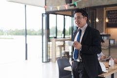 Geschäftsmann, der an Hand weißen Tasse Kaffee steht und hält erfolgreicher Konzept- und Kopienraum des Geschäfts für Text stockfoto