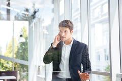 Geschäftsmann, der am Handy im Büro steht und spricht Lizenzfreie Stockfotografie