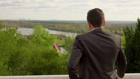 Geschäftsmann, der am Handy spricht und den schönen Park betrachtet stock video footage