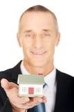 Geschäftsmann, der Hausmodell hält Stockfotos