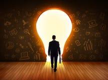 Geschäftsmann, der helle Glühlampe in der Wand betrachtet Stockfotografie