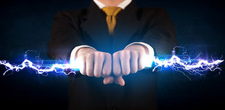 Geschäftsmann, der hellen Bolzen des Stroms in seinen Händen hält Lizenzfreies Stockbild