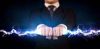 Geschäftsmann, der hellen Bolzen des Stroms in seinen Händen hält Stockfotos