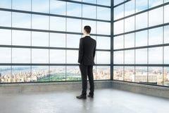 Geschäftsmann, der heraus das Fenster des leeren Dachbodenraumes schaut Lizenzfreies Stockbild