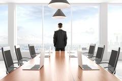 Geschäftsmann, der heraus das Fenster im modernen Konferenzsaalesprit schaut Lizenzfreie Stockbilder