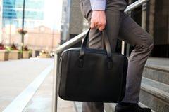 Geschäftsmann, der hinten einen ledernen Aktenkoffer in seiner handss modernen Stadt geht und hält stockfotografie