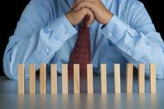 Geschäftsmann, der hinter dem hölzernen Block in der Reihe, Metapher zu b denkt Stockfoto