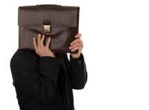 Geschäftsmann, der hinter einem Aktenkoffer lokalisiert auf weißem backgrou sich versteckt Lizenzfreies Stockbild