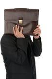 Geschäftsmann, der hinter einem Aktenkoffer lokalisiert auf weißem backgrou sich versteckt Lizenzfreie Stockbilder