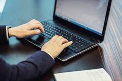 Geschäftsmann, der hinter einem Laptop, ernstes Geschäftsmannsitzen sitzt Stockfoto