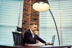 Geschäftsmann, der hinter einem Laptop, ernstes Geschäftsmannsitzen sitzt Stockfotografie