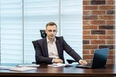Geschäftsmann, der hinter einem Laptop, ernstes Geschäftsmannsitzen sitzt Lizenzfreie Stockfotografie