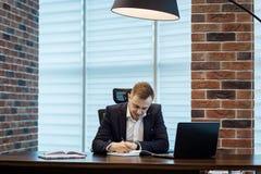 Geschäftsmann, der hinter einem Laptop, ernstes Geschäftsmannsitzen sitzt Stockbild