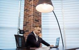 Geschäftsmann, der hinter einem Laptop, ernstes Geschäftsmannsitzen sitzt Lizenzfreies Stockbild