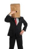 Geschäftsmann, der hinter Papierbeutel sich versteckt Lizenzfreies Stockfoto