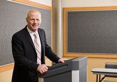 Geschäftsmann, der hinter Podium steht Lizenzfreies Stockbild