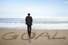 Geschäftsmann der hinteren Ansicht, der mit Zielwort auf Sandstrand steht Lizenzfreie Stockfotos