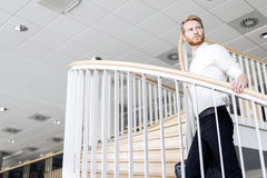 Geschäftsmann, der hinunter die Treppe geht, während, eine Tasche halten Stockfoto