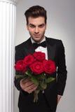 Geschäftsmann, der Ihnen einen Blumenstrauß von roten Rosen gibt Stockbilder