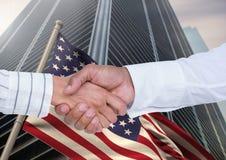 Geschäftsmann, der ihre Hände gegen amerikanische Flagge und Wolkenkratzer rüttelt Stockfotografie