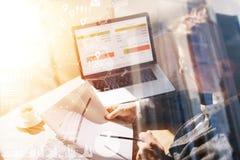 Geschäftsmann, der im Büro auf Laptop arbeitet Mann, der Papierdokumente in den Händen verwahrt Konzept des digitalen Schirmes, v stockfotografie
