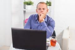 Geschäftsmann, der im Büro, bei Tisch sitzend arbeitet Lizenzfreie Stockfotos