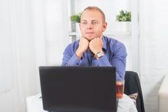 Geschäftsmann, der im Büro, bei Tisch sitzend mit einem Laptop arbeitet Stockfoto