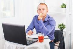 Geschäftsmann, der im Büro, bei Tisch sitzend mit einem Laptop arbeitet und schauen Kamera Lizenzfreies Stockfoto
