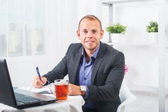 Geschäftsmann, der im Büro, bei Tisch sitzend mit einem Laptop arbeitet und schauen lächelnd Stockfotos