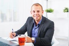 Geschäftsmann, der im Büro, bei Tisch sitzend mit einem Laptop arbeitet und schauen lächelnd Stockbild