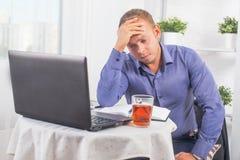 Geschäftsmann, der im Büro, bei Tisch sitzend mit einem Laptop Franc arbeitet Stockfotos