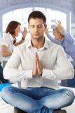 Geschäftsmann, der im Büro meditiert Lizenzfreie Stockfotos