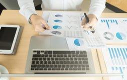 Geschäftsmann, der im Büro mit Laptop, Tablette und Dokumenten arbeitet Stockfotografie