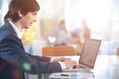 Geschäftsmann, der im Büro mit Laptop-, Tabletten- und Diagrammdatendokumenten arbeitet Lizenzfreies Stockbild
