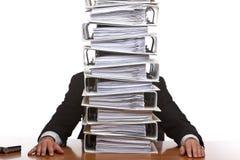 Geschäftsmann, der im Büro mit sehr großer Schreibarbeit sitzt Lizenzfreies Stockbild