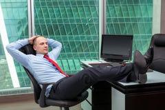 Geschäftsmann, der im Büro sich entspannt Lizenzfreie Stockfotografie