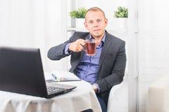 Geschäftsmann, der im Büro, sitzend an einem Tisch arbeitet, der eine Schale hält und gerade schaut Stockfoto