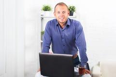 Geschäftsmann, der im Büro, sitzend an einem Tisch arbeitet, der Schale hält und gerade schaut Stockfoto