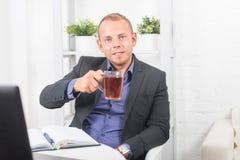 Geschäftsmann, der im Büro, sitzend an einem Tisch arbeitet, der Schale hält und gerade schaut Lizenzfreies Stockbild