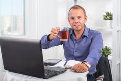 Geschäftsmann, der im Büro, sitzend an einem Tisch arbeitet, der Schale hält und gerade schaut Stockbild