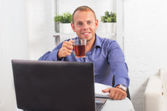 Geschäftsmann, der im Büro, sitzend an einem Tisch arbeitet, der Schale hält und gerade schaut Stockbilder
