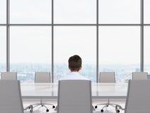 Geschäftsmann, der im Büro sitzt Stockbild