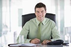 Geschäftsmann, der im Büro sitzt Stockbilder