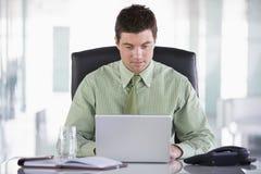 Geschäftsmann, der im Büro sitzt Lizenzfreie Stockbilder