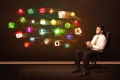 Geschäftsmann, der im Bürostuhl mit Tablette und buntem AP sitzt Stockfotos