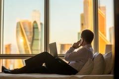 Geschäftsmann, der im Hotelzimmer arbeitet lizenzfreies stockbild