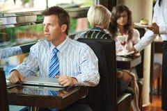 Geschäftsmann, der im Kaffee sitzt Stockbild