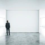 Geschäftsmann, der im leeren Büro steht Stockbilder