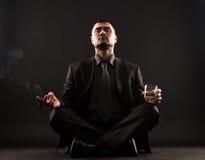 Geschäftsmann, der im Lotussitz, meditateing sitzt Stockfotografie