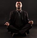 Geschäftsmann, der im Lotussitz, meditateing sitzt Lizenzfreie Stockfotografie